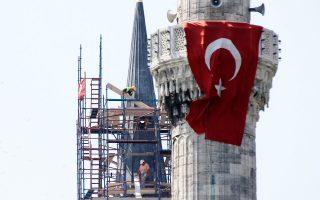 Δύο άνδρες εργάζονται έξω από τον μιναρέ του Μπλε Τζαμιού στην Κωνσταντινούπολη.