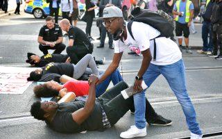 Κάτοικος του Νότιγχαμ σφίγγει το χέρι νεαρού μαύρου, ο οποίος πραγματοποιεί καθιστική διαμαρτυρία κατά της αστυνομικής βίας, στις 5 Αυγούστου, στην πόλη της κεντρικής Αγγλίας.