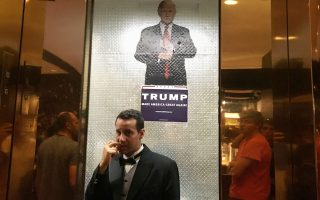 Προβληματισμένος δείχνει ο υπάλληλος του Πύργου Τραμπ στη Νέα Υόρκη καθώς στέκεται κάτω από αφίσα του ιδιοκτήτη σε ανελκυστήρα του κτιρίου.