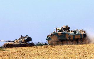 Τουρκικό τανκς και θωρακισμένο όχημα έχουν σταθμεύσει κοντά στα σύνορα με τη Συρία, στο Καρκαμίς της Τουρκίας.