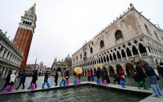 Πανέμορφη, ακόμα και πλημμυρισμένη, η πλατεία του Αγίου Μάρκου στη Βενετία. Η πόλη, όμως, κινδυνεύει λόγω της υπέρμετρης τουριστικής ανάπτυξης και κάποιων έργων μεγάλης κλίμακας. Η Unesco κρούει τον κώδωνα του κινδύνου τοποθετώντας τη Γαληνοτάτη στη λίστα των Μνημείων Παγκόσμιας Κληρονομιάς που κινδυνεύουν, επισημαίνοντας ότι οι συνεχιζόμενες αλλαγές θα διαταράξουν την ευαίσθητη ισορροπία ανάμεσα στην πόλη και τη λιμνοθάλασσα.