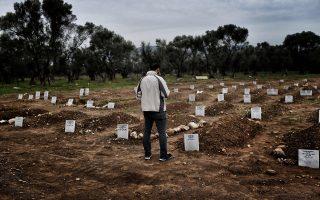 Πρόσφυγας προσεύχεται στο κοιμητήριο του χωριού Κάτω Τρίτος στη Λέσβο, που δημιουργήθηκε για θύματα ναυαγίων.