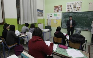 O δήμαρχος Αθηναίων Γιώργος Καμίνης μπροστά από τον πίνακα μιλάει σε μαθητές κατά την επίσκεψή του στο Κοινωνικό Φροντιστήριο του δήμου Αθηναίων.