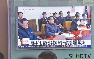 Πολίτες στον σιδηροδρομικό σταθμό της Σεούλ παρακολουθούν τηλεοπτικό ρεπορτάζ για τη θρυλούμενη εκτέλεση του Κιμ Γιονγκ Τζιν, υπουργού Παιδείας της Βόρειας Κορέας.