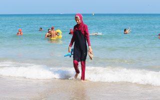 Νεαρή μουσουλμάνα βγαίνει από τη θάλασσα σε παραλία της Μπιζέρτα της ΒΑ Τυνησίας, φορώντας το μπουρκίνι της.