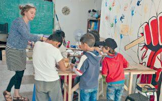 Παιδιά παρακολουθούν μάθημα τέχνης στο κέντρο εκπαίδευσης προσφύγων στη Χίο, το οποίο λειτουργούν εθελοντές.