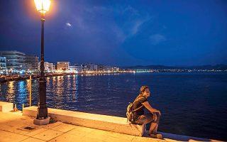 Ρεμβάζοντας στον παραλιακό πεζόδρομο, με φόντο τα φώτα της πόλης του Λουτρακίου.