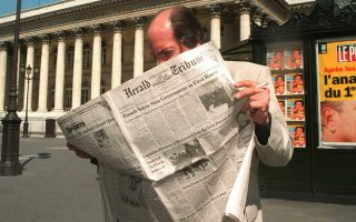 (FILES) This file photo taken on May 26, 1997 shows a man reading the International Herald Tribune in front of the Bourse in Parisa day after the first round vote of the legislative elections.   The editorial production room of the International New York Times, a fixture of Paris life for nearly 130 years as the International Herald Tribune, closed on September 28, 2016, staff said. Editorial production of the international version of the New York Times in Paris stopped a few days ago under a plan that the owners announced in April. / AFP / PIERRE BOUSSEL