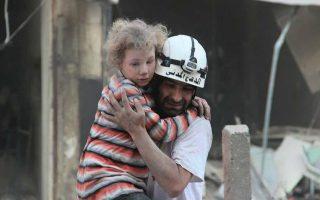 Εθελοντής της ανθρωπιστικής οργάνωσης «Λευκά Κράνη» μεταφέρει ένα παιδάκι που γνώρισε τη φρίκη των βομβαρδισμών στο Χαλέπι.