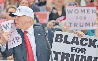 Αφίσα με το σύνθημα «Γυναίκες υπέρ του Τραμπ» φιλάει ο Ρεπουμπλικανός υποψήφιος πρόεδρος κατά τη διάρκεια της χθεσινής ομιλίας του στη Φλόριντα.