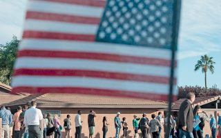 Αναμονή κάτω από τον ήλιο της Αριζόνας. Η αλλαγή της σύνθεσης του αμερικανικού εκλογικού σώματος, με την αύξηση των ισπανόφωνων και μαύρων ψηφοφόρων, ευνοεί τη Χίλαρι Κλίντον, η οποία ωστόσο χάνει την επαφή της με μερίδα της εργατικής τάξης, προς όφελος του Ντόναλντ Τραμπ. Η υποψηφιότητα της Κλίντον συγκίνησε γυναίκες που στόλισαν χθες τα μνήματα σουφραζετών με αναμνηστικά της ψήφου τους.