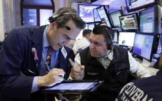 Traders Gregory Rowe, left, and Robert Finnerty work in their booth on the floor of the New York Stock Exchange, Wednesday, Nov. 9, 2016. Stocks are moving solidly higher in midday trading on Wall Street following Donald Trump's upset victory over Hillary Clinton in the U.S. presidential election. (AP Photo/Richard Drew)