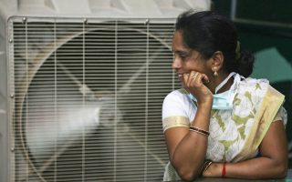 Mία γυναίκα δροσίζεται μια ζεστή καλοκαιρινή ημέρα στην Ιντερμπάντ της Ινδίας.