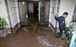 Πυροσβέστες αντλούν νερά από πλημμυρισμένη είσοδο πολυκατοικίας στον περιφερειακό του Λυκαβηττού.