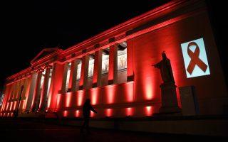 Η σκιά μιας γυναίκας μπροστά στο φωτισμένο με κόκκινους προβολείς Πανεπιστήμιο Αθηνών ολοκληρώνει τον συμβολισμό του αγώνα κατά του AIDS, που ενώνει Ευρώπη και Ανατολή και στοχεύει στην ενημέρωση του κοινού και στην ανάγκη να λείψει η απειλή κατά της ανθρωπότητας (φωτογραφία Γιάννης Κολεσίδης).