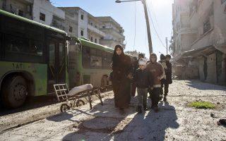 Σύροι του Ανατολικού Χαλεπίου κατευθύνονται στα λεωφορεία που τους περιμένουν για να τους μεταφέρουν σε ασφαλέστερα σημεία της χώρας.