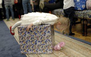 Είναι δικό μου! Η μόλις 3 ετών Grigolre Nicole Isabela είναι ξάπλα πάνω στο δώρο της, σε επίσημη εκδήλωση που διοργάνωσε το υπουργείο Εθνικής Άμυνας της Ρουμανίας. Η χριστουγεννιάτικη γιορτή  ήταν αφιερωμένη στις οικογένειες των πεσόντων ηρώων της χώρας σε Αφγανιστάν και Ιράκ.  EPA/ROBERT GHEMENT