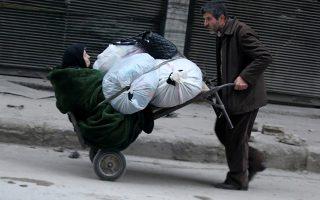Φύγαμε! Το μειδίαμα στο στόμα της δεν μαρτυρά αν έχει αφορμή την δύσκολη στιγμή στην οποία έχει περιέλθει ή την λύπη για τον βαστάζο (μάλλον γιο της) που κουβαλά τόσο φορτίο. Πάντως και οι δυο τους φεύγουν από το σπαρασσόμενο Χαλέπι.  REUTERS/Abdalrhman Ismail