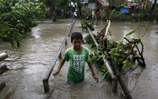 epa05688402 A Filipino teen wades through flood water in the typhoon-hit town of Pamplona, Camarines Sur, Philippines, 26 December 2016. According to an Office of Civil Defense (OCD) report on 26 December, hundreds of thousands of villagers spent their Christmas day in evacuation centers in Bicol region, many flights were cancelled at Manila's international airport, and scores of sea vessels have reportedly sunk as Typhoon Nock-ten brought howling winds and strong rains in central Philippines.  EPA/FRANCIS R. MALASIG