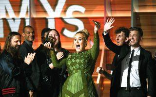 Η Αντέλ, μεγάλη νικήτρια της βραδιάς, επιδεικνύει ένα (σπασμένο) από τα 5 συνολικά βραβεία που παρέλαβε.
