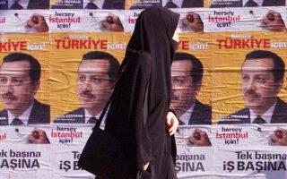 Γυναίκα περνάει μπροστά από προεκλογικές αφίσες του AKP το 2002, στην Κωνσταντινούπολη.