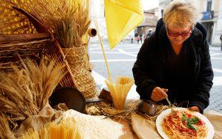 Μια γυναίκα απολαμβάνει ένα πιάτο μακαρόνια με ντομάτα και βασιλικό σε αγροτική έκθεση στη Ρώμη.