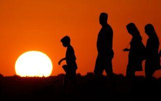 Ο ήλιος δύει, ενώ τουρίστες επισκέπτονται, μια ημέρα καύσωνα, το Μνημείο της Ελευθερίας στο Κάνσας.