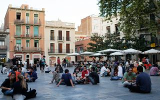Νέοι, κάτοικοι της Βαρκελώνης, απολαμβάνουν την πεζοδρόμηση δρόμου στη συνοικία Γκράσια της ισπανικής μεγαλούπολης.