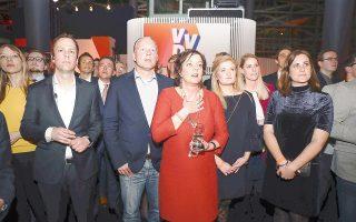 Με την ανακούφιση να αποτυπώνεται στα πρόσωπά τους, μέλη του φιλελεύθερου κόμματος VVD του πρωθυπουργού Ρούτε παρακολουθούν τα αποτελέσματα στη Χάγη.