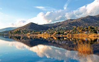 Ηλιοβασίλεμα στο παραθαλάσσιο θέρετρο της Αλυκής Βοιωτίας – η μικρή λίμνη το χωρίζει από τη θάλασσα του κόλπου των Αλκυονίδων. (Φωτογραφία: ΤΖΟΥΛΙΑ ΚΛΗΜΗ)
