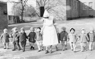 Εντεκα νήπια βγαίνουν βόλτα στην αυλή κέντρου φροντίδας στα περίχωρα του Λονδίνου, το 1941. Τα νήπια αυτά είναι ανάμεσα στα 500 παιδιά που εκκενώθηκαν από το Λονδίνο για να προστατευθούν από τους βομβαρδισμούς. (AP Photo)