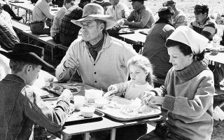Ο ηθοποιός Τσάρλτον Ίστον τρώει με την οικογένειά του σε διάλειμμα από τα γυρίσματα της τελευταίας του ταινίας «Will Penny», το 1967. (AP Photo)