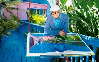 Ο Ντέιβιντ Χόκνεϊ στο σπίτι του στο Λος Αντζελες, με το λεύκωμα που πρόσφατα κυκλοφόρησε από την Taschen με αφορμή τα 60 χρόνια του στην τέχνη και στην έκθεση.