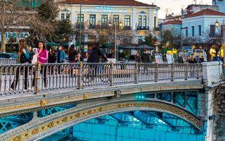 Η κεντρική πεζογέφυρα του Ληθαίου φωτισμένη και στο βάθος το ιστορικό ξενοδοχείο «Πανελλήνιο», που στεγάζεται σε νεοκλασικό των αρχών του 20ού αιώνα. (Φωτογραφία: ΔΙΟΝΥΣΗΣ ΚΟΥΡΗΣ)