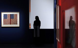 EMBARGOED UNTIL 07/03/17 0001 GMTAn employee poses next to a print of Jasper Johns' 'Flags I' at the exhibition
