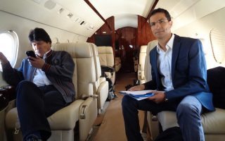 Ο Εβο Μοράλες  (αριστερά) ελέγχει τα μηνύματά του στο κινητό, στο προεδρικό αεροσκάφος με τον Ιάσονα Πιπίνη (δεξιά).