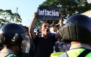 Πανό με τη λέξη «Πληθωρισμός» κρατάει οπαδός της αντιπολίτευσης σε διαδήλωση στο Καράκας.