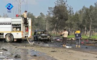 epa05909731 A handout photo made available by Thiqa News Agency (TNA) showing rescue and media personnel at the scene of a car bomb attack that targeted buses evacuating civilians from besieged towns, al-Rashideen area, west of Aleppo, Syria, 15 April 2017. According to media reports at least 24 people were killed when a suicide car attacked buses transporting civilians from Kefraya and al-Foua'a towns to al-Rashideen area near Aleppo.  EPA/THIQA NEWS AGENCY / HANDOUT  HANDOUT EDITORIAL USE ONLY/NO SALES