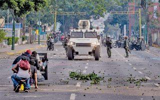 Διαδηλωτές συγκρούονται με την αστυνομία στη διάρκεια των μαζικών κινητοποιήσεων, προχθές στο Καράκας.