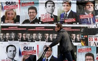 A pedestrian walks past campaign posters for the 2017 French presidential election, in Paris, France, April 5, 2017. REUTERS/Charles Platiau