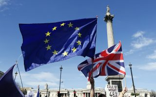 The European flag and the United Jack flag are held by Anti Brexit campaigners walking past Nelson's Column in Trafalgar Square towards Britain's parliament in London, Saturday March 25, 2017. Britain's Prime Minister Theresa May is expected to start the process of leaving the European Union on Wednesday March 29. (AP Photo/Kirsty Wigglesworth)