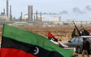 The Kingdom of Libya flag flies in front of a refinery in Ras Lanuf in this March 8, 2011, file photo.  REUTERS/Goran Tomasevic/ Files