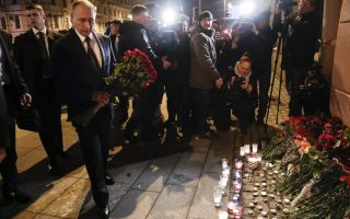Russian President Vladimir Putin, second left, lays flowers at a place near the Tekhnologichesky Institut subway station in St.Petersburg, Russia, Monday, April 3, 2017. A bomb blast tore through a subway train deep under Russia's second-largest city Monday, killing several people and wounding many more in a chaotic scene that left victims sprawled on a smoky platform. (AP Photo/Dmitri Lovetsky)