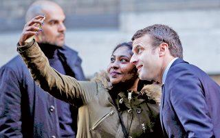 Ο Εμανουέλ Μακρόν ποζάρει για χάρη μιας νεαρής θαυμάστριάς του, έξω από την κατοικία του, στο Παρίσι.