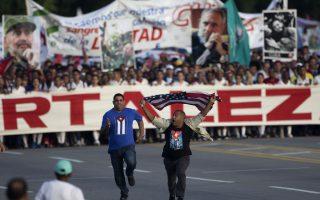 Πρωτομαγιά 1.(Γιατί να το κρύψωμεν άλλωστε;) Με μια αμερικάνικη σημαία στην κορυφή της μεγαλειώδους πορείας στην Αβάνα, έτρεχε ο άνδρας, λίγο πριν τον συλλάβουν αστυνομικοί με πολιτικά και τον πάνε στην κυριολεξία σηκωτό και μπροστά από τους δημοσιογράφους.  AP Photo/Desmond Boylan