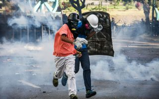 Από πυρά δακρυγόνων της αστυνομίας προστατεύονται αυτοί οι διαδηλωτές την Πέμπτη στο Καράκας.