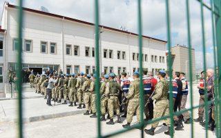 Τούρκοι στρατιώτες συνοδεύουν συναδέλφους τους χθες στα δικαστήρια των φυλακών Σινκάν, στην Αγκυρα. Οι 221 στρατιωτικοί, μεταξύ αυτών και 27 στρατηγοί, κατηγορούνται για συμμετοχή στην απόπειρα πραξικοπήματος του Ιουλίου. Στους κατηγορουμένους βρίσκεται και ο ιεροκήρυκας Φετουλάχ Γκιουλέν, ο οποίος ζει στις ΗΠΑ και θα δικαστεί ερήμην.