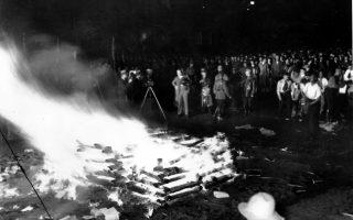 Γερμανοί πολίτες συγκεντρώνονται για να παρακολουθήσουν το κάψιμο των βιβλίων που οι ναζί έχουν χαρακτηρίσει «αντιγερμανικά», στην πλατεία «Μπέμπελ Πλατς» του Βερολίνου, το 1933. Τα βιβλία ρίχνουν στην πυρά φοιτητές, μέλη του Ναζιστικού Κόμματος, καίγοντας μεταξύ άλλων, έργα των Φρόιντ, Μαρξ, Μπρεχτ και Τσβάιχ. (AP Photo)