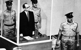 Ο Άντολφ Άιχμαν, περιτριγυρισμένος από φρουρούς, στέκεται μέσα σε γυάλινο κελί του ανωτάτου δικαστηρίου της Ιερουσαλήμ, καθώς οι δικαστές εισέρχονται στην αίθουσα, το 1962. Το δικαστήριο καταδίκασε τον λεγόμενο «αρχιτέκτονα του Ολοκαυτώματος» σε θάνατο δια απαγχονισμού για δεκαπέντε αδικήματα, μεταξύ των οποίων εγκλήματα κατά της ανθρωπότητας και του εβραϊκού λαού, απορρίπτοντας εν συνεχεία την αίτηση χάριτος που υπέβαλε ο κατηγορούμενος. (AP Photo)