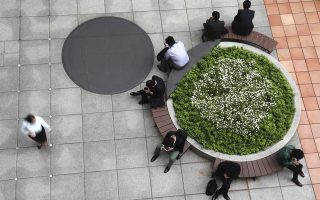 Businessmen rest on the bench in Tokyo's Shiodome business district, Wednesday, May 17, 2017. (AP Photo/Shizuo Kambayashi)